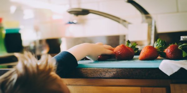 Young child reaching for strawberries on a countertop