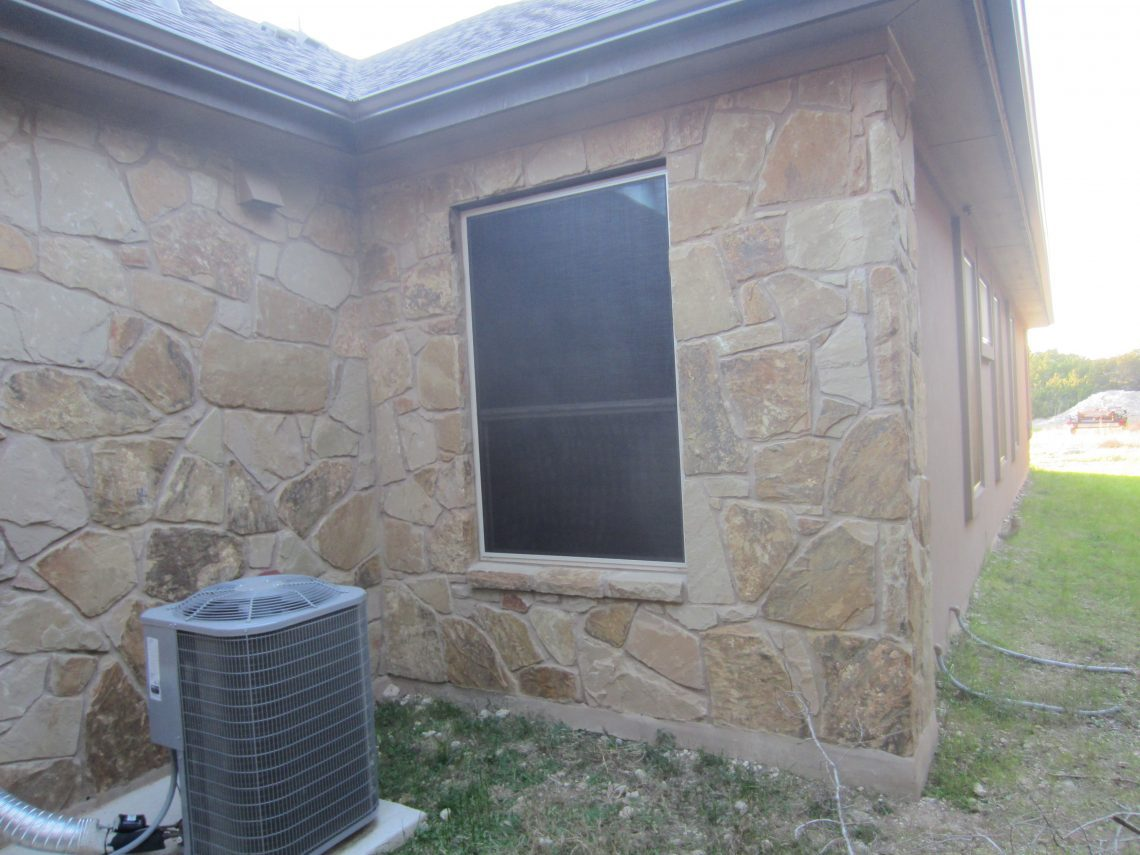 This brown solar screen fabric looks outstanding against the sand stone exterior.