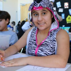A girl draws a picture at the Autism Academy, a school for autistic kids.