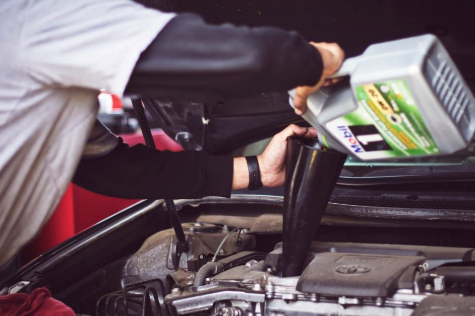 A man refills motor oil on car engine bay. Photo by Tim Mossholder for Unsplash.