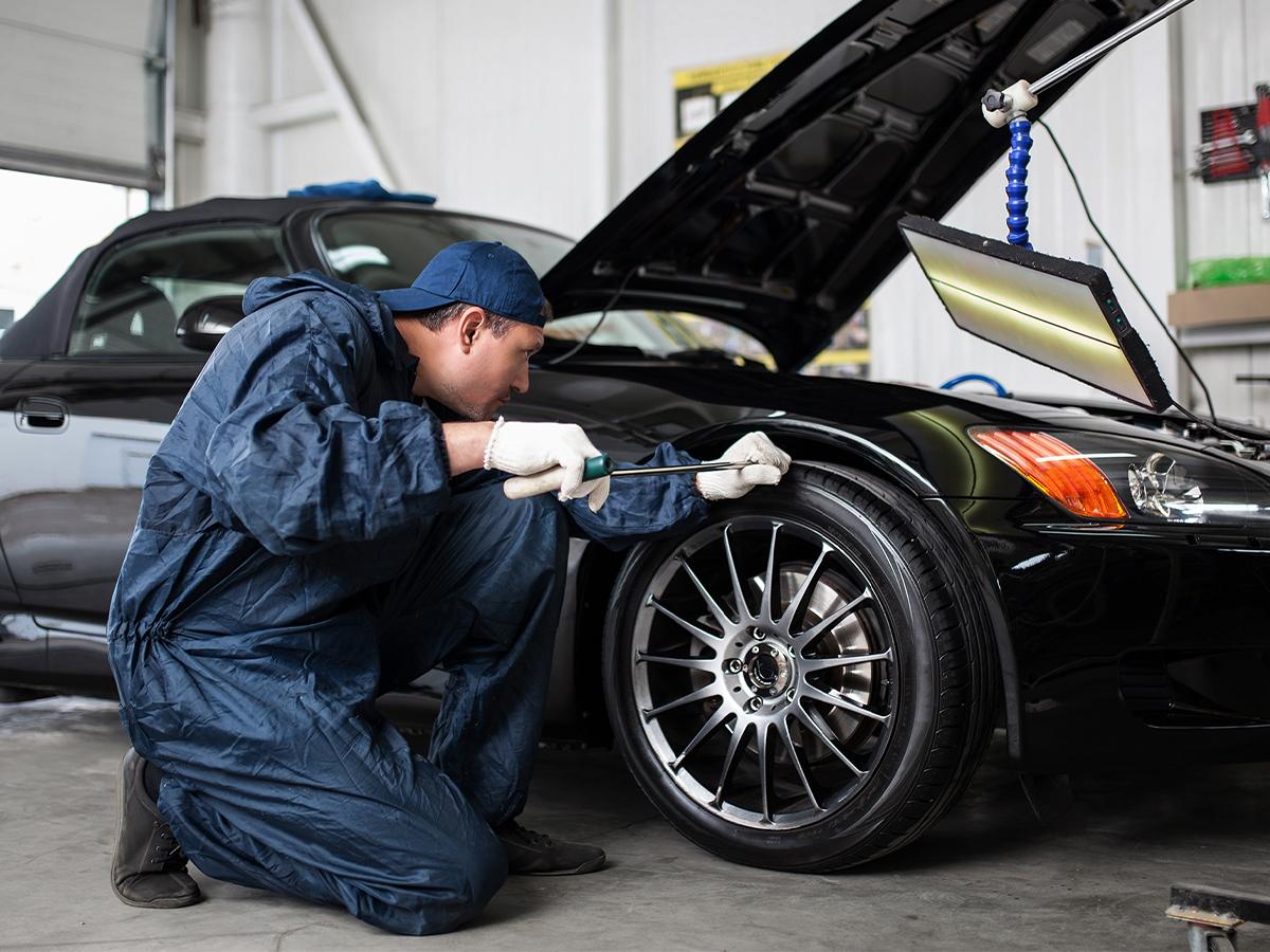 mechanic inspecting tires with open hood