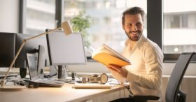 Man smiling at desk while reading Automated Lights and Shades Manhattan