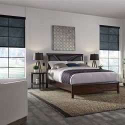 Bed and two chairs with black shades lowered Automated Lights and Shades Manhattan