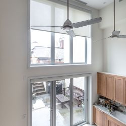 Large ceiling fans in front of window with white shades lowered Automated Lights and Shades Manhattan