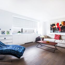 Couch, chair, wood floors, and white shades lowered Automated Lights and Shades Manhattan