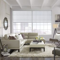 White couch in front of lowered wide shades Automated Lights and Shades Manhattan