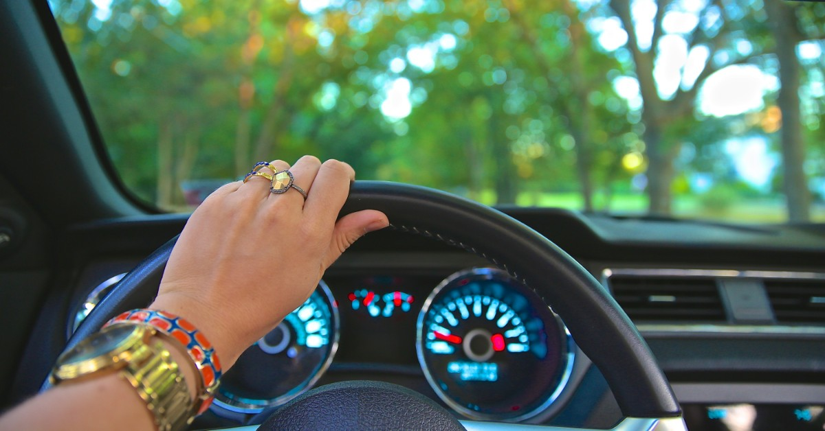 Hand holding a steering wheel while driving along a tree-lined street.