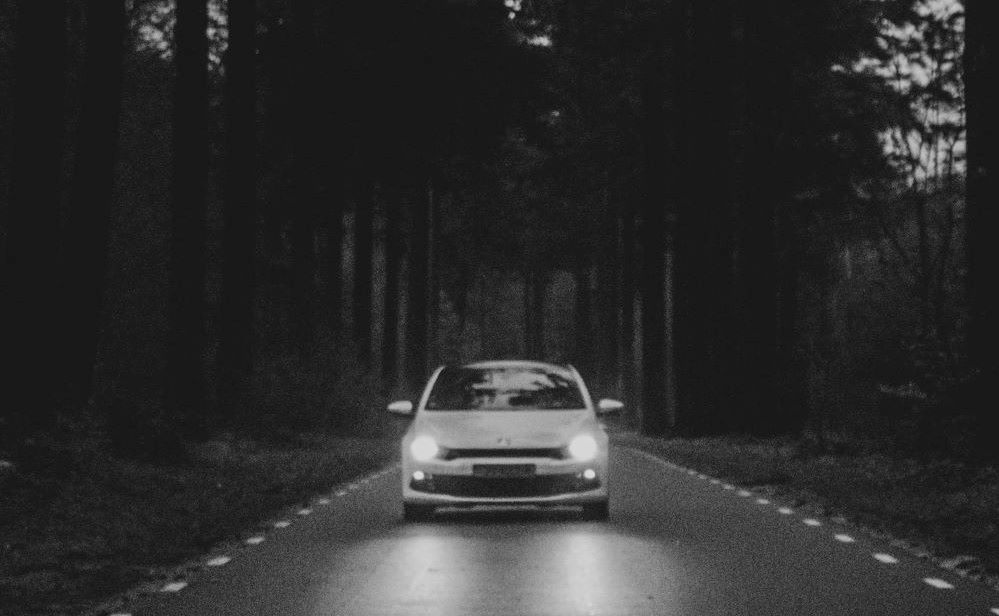 A car passes through a road in the middle of a wooded forest. Photo by Jorgen Hendriksen on Unsplash.