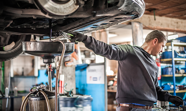 Mechanic changing car's oil