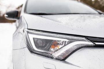 Closeup of a Vehicle Headlight and Hood in the Snow
