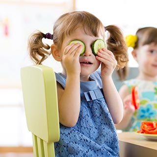 Little Girl Holding Cucumbers Over Her Eyes