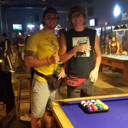 Image of two men posing for the camera before playing pool