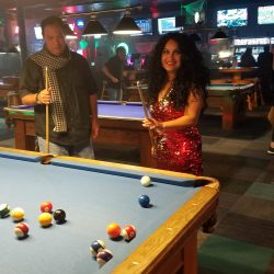 Image of woman smiling while playing pool