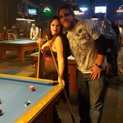 Image of happy couple posing for the camera at the pool table