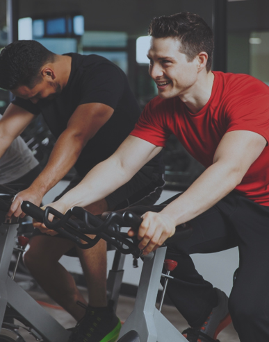 A pair of young men use elliptical.