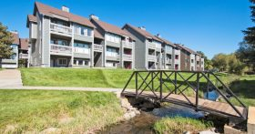 A view of The Landmark Apartments in Fort Collins with a small bridge and stream out front.