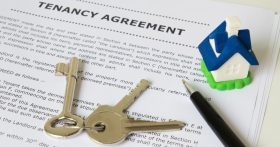 "A ""Tenancy Agreement"" document with a pen and keys on top."