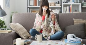 A woman sits, bundled on her couch with tissues and a mug.