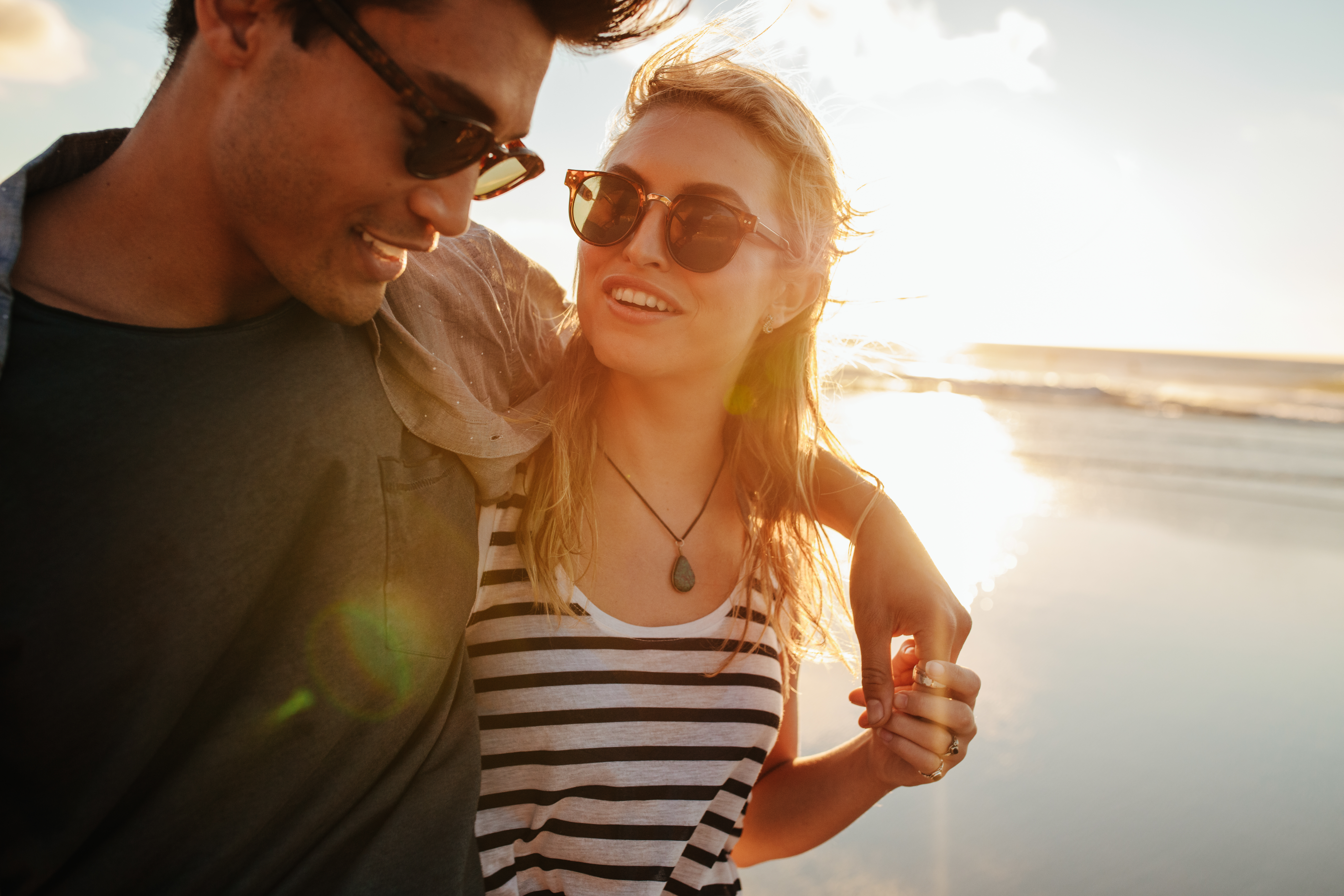 Man with arm around woman smiling on the beach