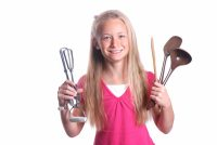 Portrait of a preteen girl child with happy smiling facial expression holding various old used cooking tools in her hands. Image isolated on white studio background.