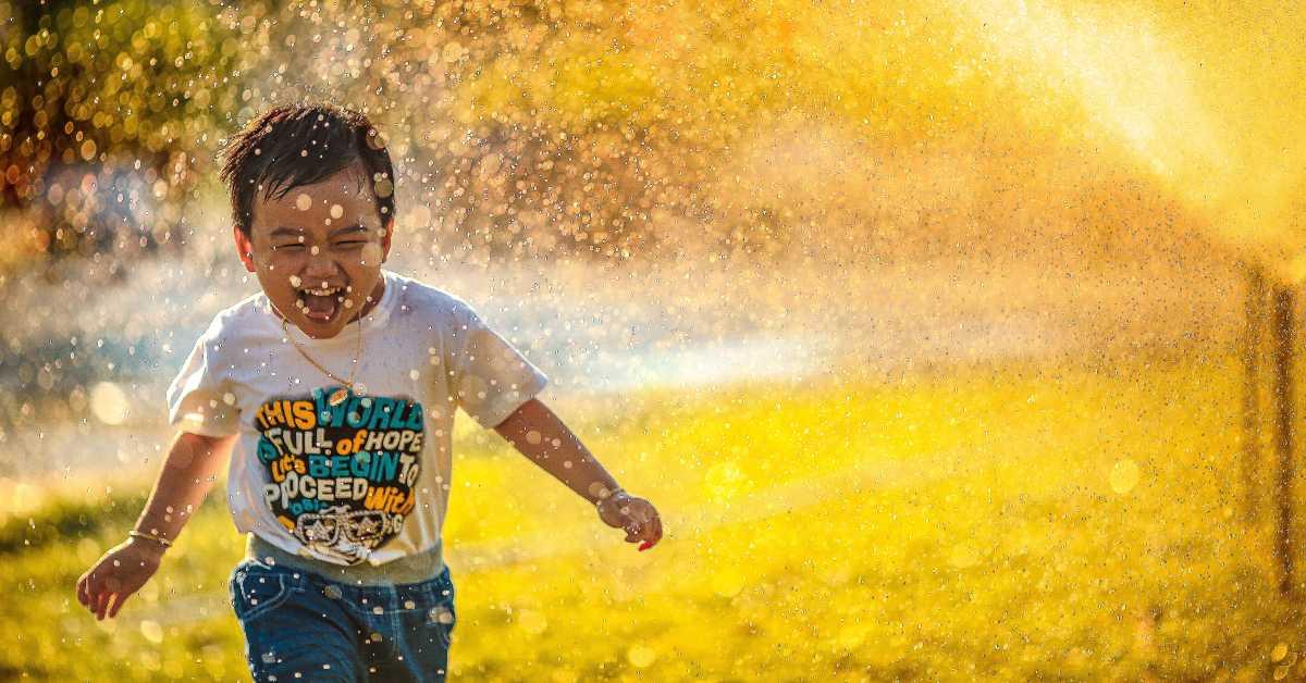 Photo of a boy running through sprinklers by MI PHAM on Unsplash