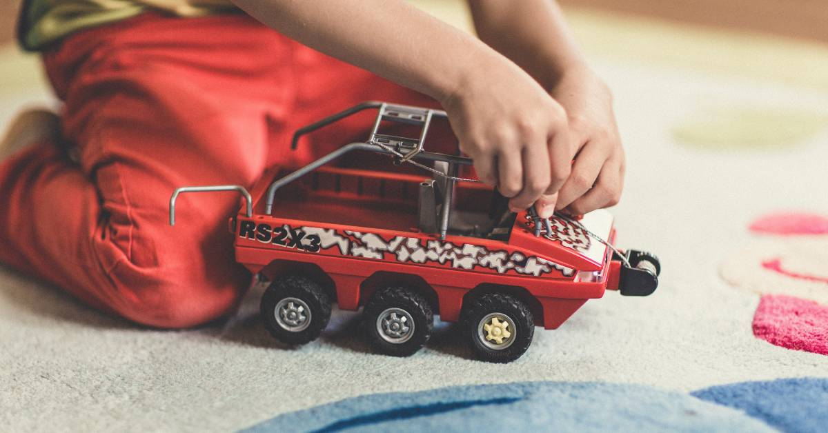 Photo of a child playing with a truck by Markus Spiske on Unsplash