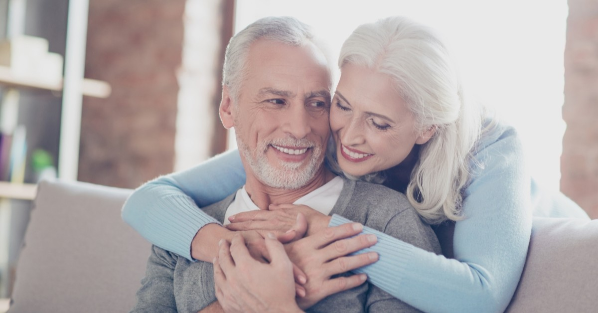 An elderly couple hugs while seated.