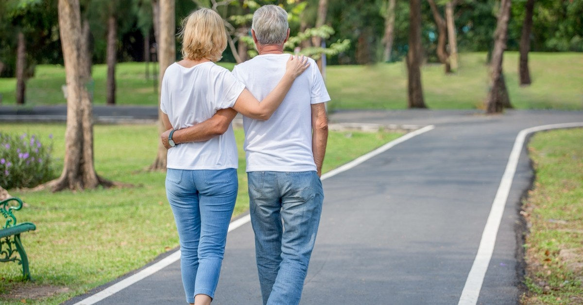 An image of a senior couple walking on a path
