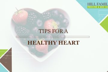"""A heart shaped bowl holds berries on a white table with the words """"tips for a healthy heart,"""""""
