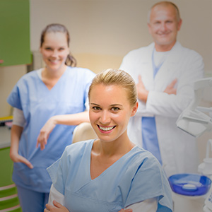A woman in blue scrubs smiles at the camera with a doctor and other nurse behind her