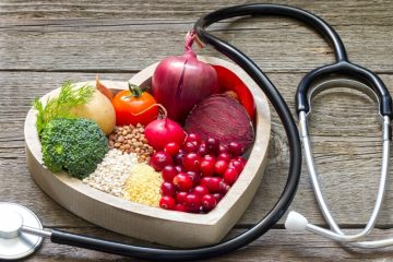 A heart shaped bowl holds a selection of fruits and veggies, surrounded by a stethoscope.