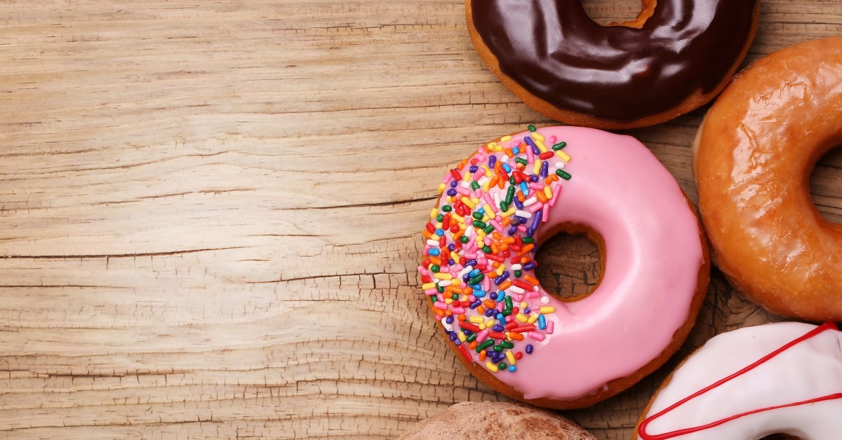 A selection of doughnuts on a light wood grain tablel