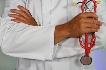 A doctor in a white lab coat holds a red stethoscope in his hands