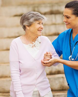 A nurse in blue scrubs helps an elderly woman down some steps