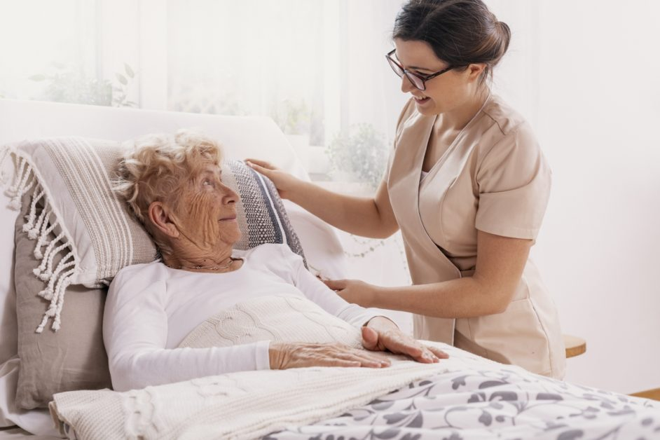 older woman in bed being attended by nurse