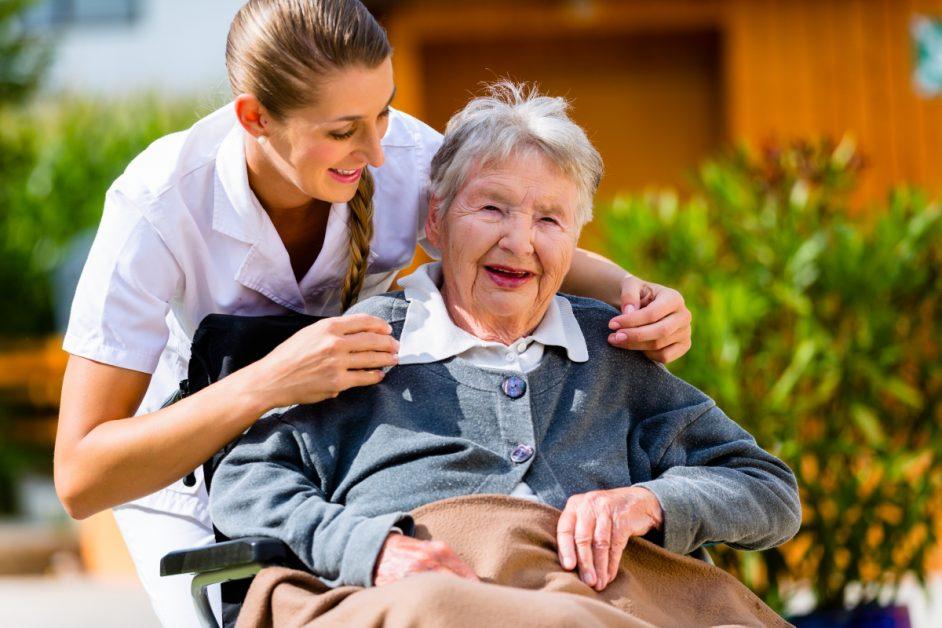 nurse helping smiling older woman in garden