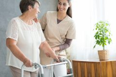 young woman helping older woman walk with aid of walker