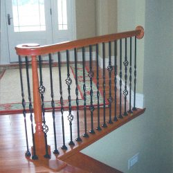 Curled wood banister rail by Bailey Custom Woodworking.