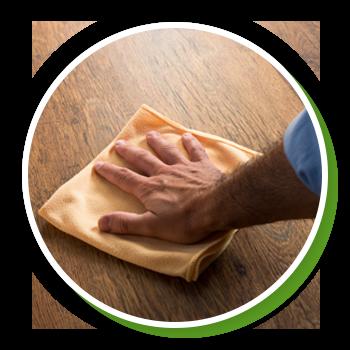 Man's hand wipes a wash cloth on hardwood flooring