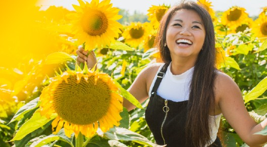 person smiling in sunflowers