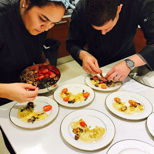 Professional personal chefs preparing plates for a special event.