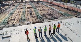 Image of construction workers standing on top of a building and looking at work they've completed.
