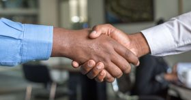 Image of two men wearing dress shirts and shaking hands.