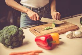 Cropped image of beautiful young girl cutting vegetables while cooking in kitchen at home