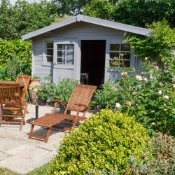 gray backyard cottage with wooden lawn chairs