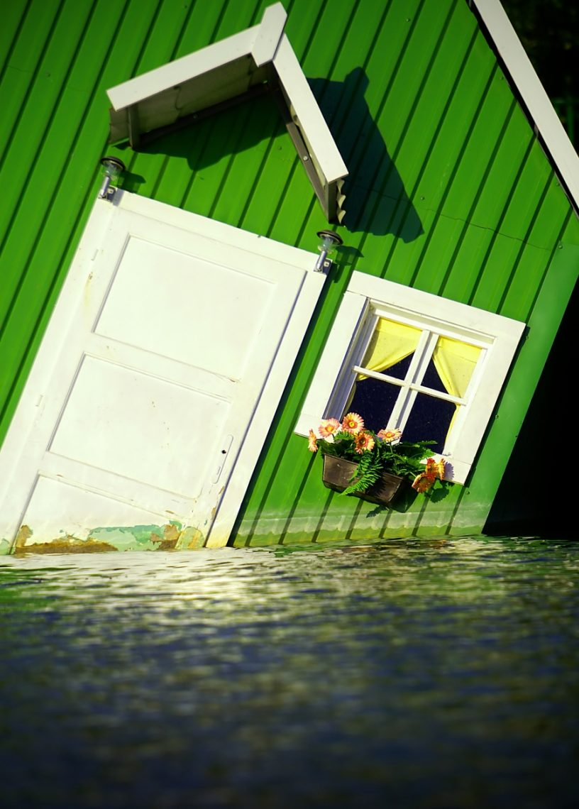 A green home flooding with water.