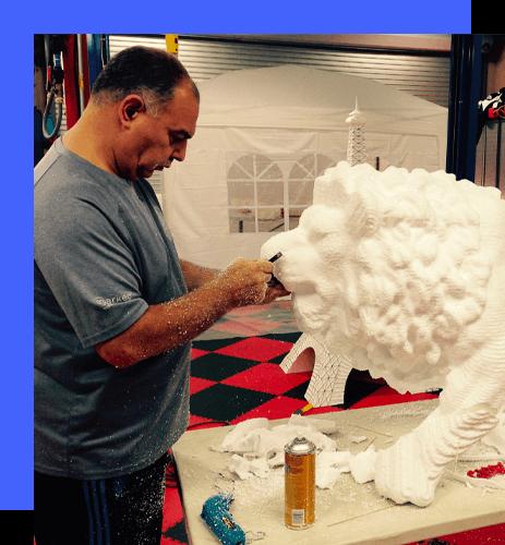 Man carving foam lion prop