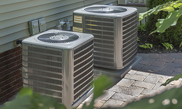 A two-unit AC installation next to a house