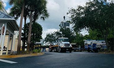 1st image of a crane raising an AC off of an air conditioning contractor's truck