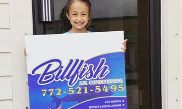 A small child holding a Billfish AC banner